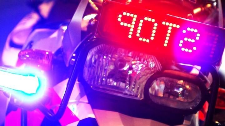 Normal surveillancemotor met zwaailicht en stopbord